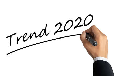 business man hand writing word trend 2020 with black color marker pen isolated on white background.TRENDS 2020 Business Concept