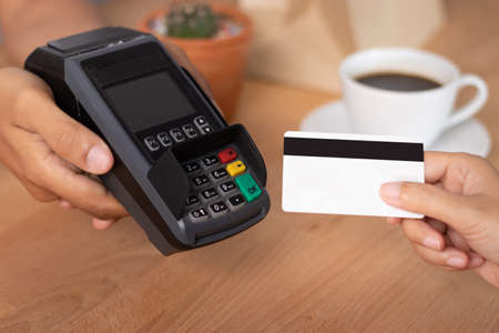 hand of customer using credit cart for payment at point of sale terminal in shop during shopping time, cashless technology and credit card payment concept