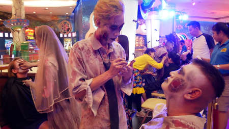 PATTAYA, THAILAND - OCTOBER 31, 2018: Foreign tourist enjoy for making ghost face painting during Halloween Festival in Pattaya, Thailand on OCTOBER 31, 2018