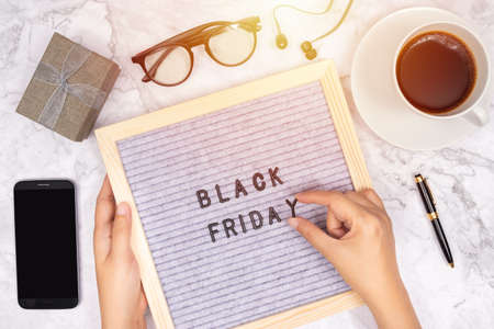 word Black Friday on letter board on white marble desk background with coffee cup ,gift box and smart phone with blank screen
