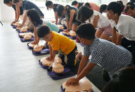 BANGKOK, THAILAND - OCTOBER 6, 2019 : a part of children and adult , participant of CPR First Aid Training course using hand pump on chest of dummy for primary safe life in Bangkok, Thailand