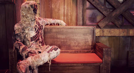 mummy model of the dead man with white bone wrapped in a cloth sit on a bench with copy space for Halloween background Banco de Imagens