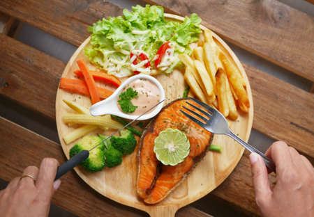 salmon steak served on wooden plate ,side dishes are boiled vegetables , French fries , fresh salad ,cream sauce and piece of lemon on top