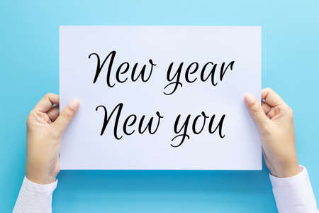 hand holding white paper with text New Year New You isolated on blue background. business goal , objective , motivation and inspiration concepts Banco de Imagens