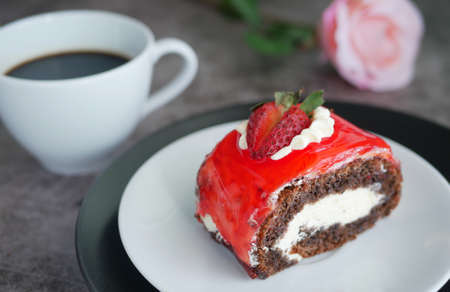 chocolate cake with strawberry jam sauce topped with whipped cream and fresh strawberry chopped served on white plate with a cup of black coffee, blur rose at background Banco de Imagens