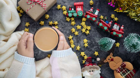 hand holding hot drink in winter season with Christmas background decorations and gift boxes on table