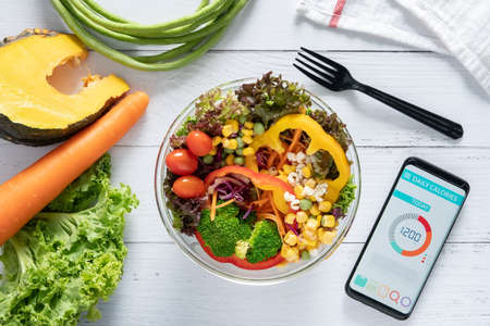 Calories counting , diet , food control and weight loss concept. Calorie counter application on smartphone screen at dining table with salad, fruit juice, bread and vegetable