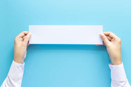 close up hands holding empty white blank horizontal paper for flyer or invitation mock up isolated on a blue background. Stockfoto