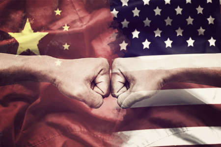 trade war between USA and China concept. two clenched fists punch each other on USA and China flag background Stockfoto