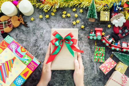 hand holding gift box from shopping bag during Christmas season and gift festival, decorations with Christmas ornament on table