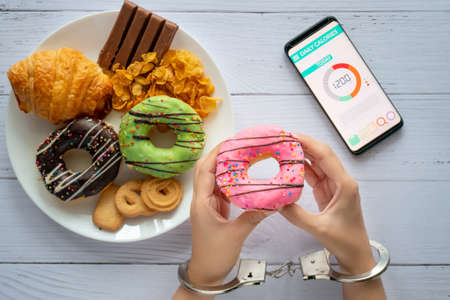 Calories control, food diet and weight loss concept. top view of two hands was control by handcuff, holding doughnut with Calorie counter application on smartphone on dining table