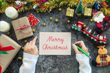 hand writing Merry Christmas on greeting card during Christmas season and gift festival, decorations with Christmas ornament on table Stockfoto