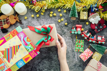 hand holding Christmas gift box from shopping bag during Christmas season and gift festival, decorations with Christmas ornament on table