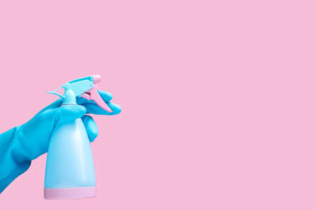 hand in blue rubber glove holding cleaning spray bottle detergent isolated on pink background with copy space for text or logo