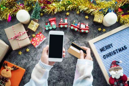online shopping for Christmas season and gift festival. hand holding mobile phone with blank screen and credit card for shopping online, decorations with Christmas ornament on table Stockfoto