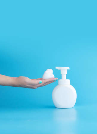 plastic pump bottle and mousse foam or cleansing foam on woman hand isolated on blue background, vertical with copy space. cleaning concept