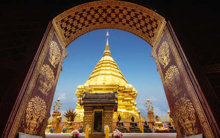 golden pagoda view through from ancient door architrave arch at Wat Phra That Doi Suthep temple. popular famous tourist temple attraction landmark in Chiangmai, Thailand