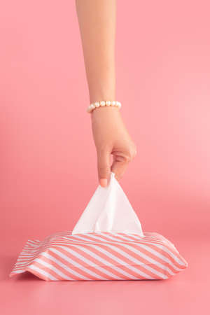 woman pull the tissue paper out of the tissue box isolated on pink background, vertical. sanitation and hygiene facility concept