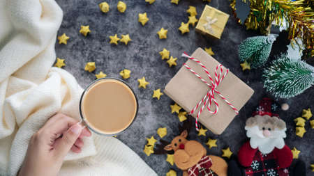 hand holding a cup of hot coffee in winter season with Christmas background decorations and gift boxes on table