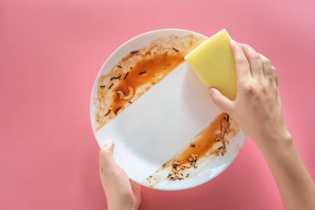 woman using yellow cleaning sponge to clean up and washing food stains and dirt on white dish after eating meal isolated on pink background. cleaning , healthcare and sanitation at home concept Stockfoto