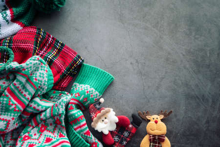 green sweater and red scotch blanket laying on the cement background with a Santa Claus doll and a reindeer for Christmas ornament with copy space