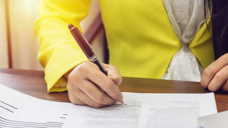 business women in yellow suite use pen sign the signature of consent in the contract agreement document. business partnership and legal agreement of lawyer concept