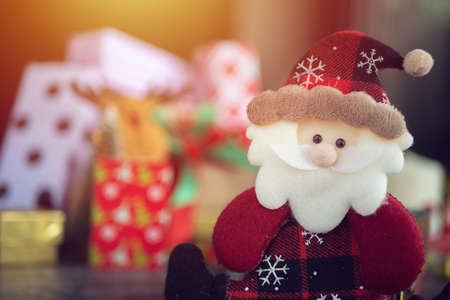Santa Claus doll, gift box present and christmas ornament for christmas greeting seasonal background. selective focus Stockfoto