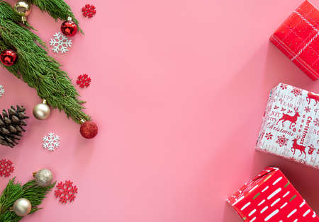 green pine, pine cone, snowflakes, Christmas ornaments and gift box in red wrap paper on pink background with copy space