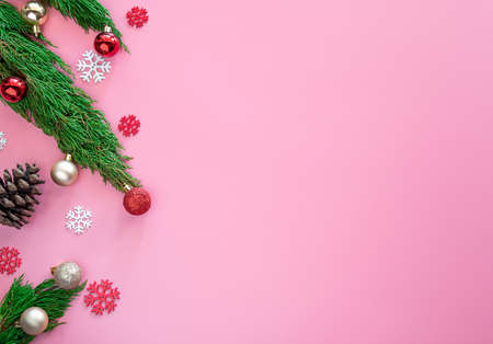 green pine, pine cone, snowflakes, red Christmas ornaments ball on pink background with copy space
