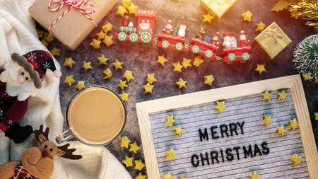 a cup of hot coffee in winter season with text Merry Christmas on letter board , Christmas ornament decorations and gift box on table for Christmas background