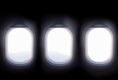three airplane windows open white window shutter wide out to view of mountain hilltop during travel by air