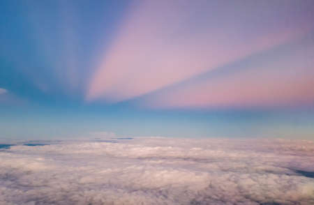 beautiful pastel sky atmosphere over white puffy cloud before sunset as seen through window of airplane, plane window. travel by airplane