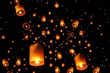 swarms of sky floating lanterns are launched into the air during New years eve and Yee Peng lantern festival traditional at Chiang Mai , Thailand.