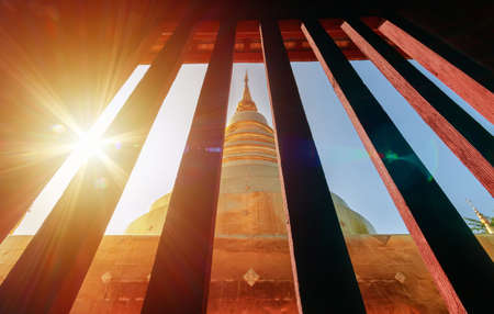 golden pagoda view from vintage window at Wat Phra Singh in Chiang Mai, Thailand with light flare in the morning. travel destination landmark Stockfoto - 135977155