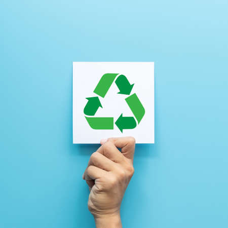 green recycling symbol on white paper card in hand isolated on blue background. green business concept for environment awareness  company