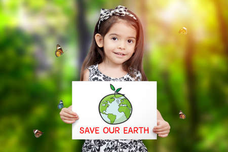 children hold paper drawing Earth and green seedling growth and word save our Earth with green tree background and butterfly flying around. children care for environmental awareness. Earth Day concept
