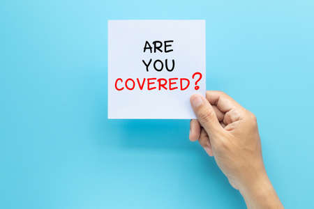 hand holding paper with question ARE YOU COVERED? isolated on blue background with copy space. travel insurance concept