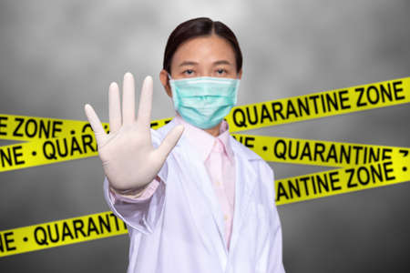 Asian female doctor wear a medical mask, raise hand for stop sign to do not enter quarantine area with yellow quarantine sign on the back, entrance is forbidden in quarantine zone. 写真素材