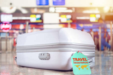 travel bag at the airport with travel insurance tag on suitcase holder for cover delay or lost luggage, trip cancellation, accident, losses, etc to protection your trip.