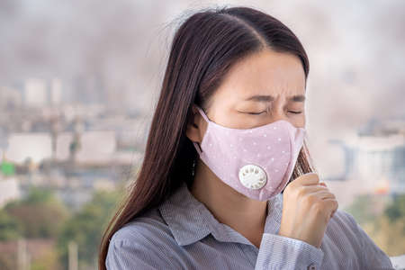 PM2.5. people feeling sick from air pollution, environment has harmful or poisonous effects. woman in the city wearing face mask to protect herself because level of pollution in the air is rising.