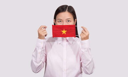 Asian woman wearing hygienic face mask painting Vietnam flag to protect from the Coronavirus 2019 (COVID-19) infection outbreak situation