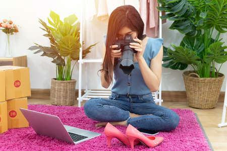 Asian woman take photo of shoe, fashion accessories for upload and selling online on website with many parcel box for shipping delivery. owner of small business working from home during self isolation
