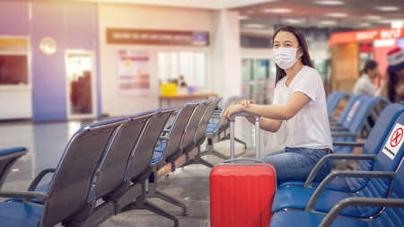 Asian tourist with luggage ,wearing hygienic mask and sit on chair with social distancing to prevent pandemic during travel at airport terminal. new normal after coronavirus, covid-19 virus epidemic Stockfoto