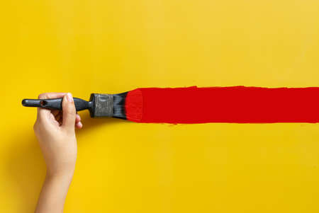 hand holding paint brush, painted red color isolated on yellow background with copy space. home improvement concept