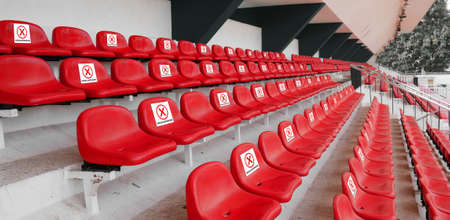 seat for sport audience, spectator with sign do not sit to for space on each chair at football sport stadium for physical distancing during coronavirus or covid-19 virus pandemic situation. new normal