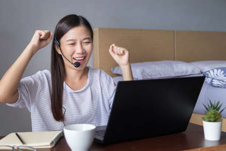 Asian woman working at home with headset making video conference with colleagues via laptop computer , feeling happy excited with arms up gesture Stockfoto