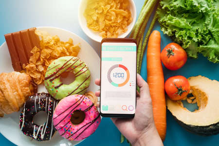 Calories counting and food control concept. woman using Calorie counter application on her smartphone with fresh vegetables, dessert and donuts on dining table Stockfoto