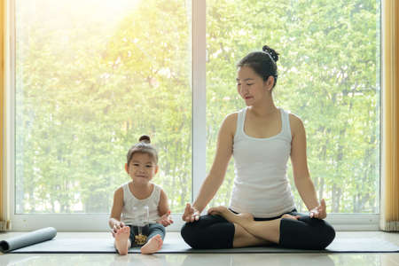 Asian mother practiced yoga by sitting in lotus position at home with a daughter sitting beside and enjoy eating snack with smiling face while workout at home. mom and kid doing activity at home