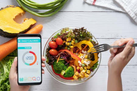 Calories counting , diet , food control and weight loss concept. Calorie counter application on smartphone screen at dining table with salad, fruit juice, bread and fresh vegetable. healthy eating Stockfoto