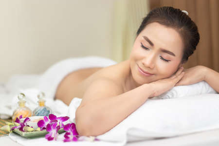 portrait of beautiful young Asian woman naked back, lay down on massage bed with relaxing  felling at beauty spa treatment. relaxing massage. advertising poster